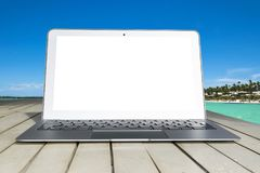Laptop computer on wooden table. Top ocean view. Tropical island background. Open blank laptop computer empty space. Front view stock photography