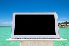 Laptop computer on wooden table. Top ocean view. Tropical island background. Open blank laptop computer empty space. Front view w Royalty Free Stock Photo