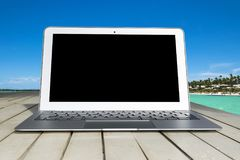 Laptop computer on wooden table. Top ocean view. Tropical island background. Open blank laptop computer empty space. Front view Royalty Free Stock Photos