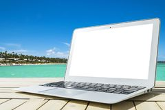 Laptop computer on wooden table. Top ocean view. Tropical island background. Open blank laptop computer empty space. Front view. With copy space. Isolated white Royalty Free Stock Photo