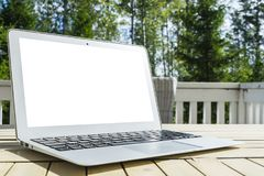 Laptop computer on wooden table. Tropical island background. Open blank laptop computer empty space. Front view with copy space. Royalty Free Stock Images
