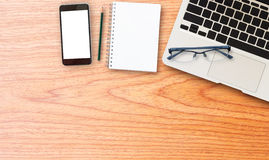 Laptop comuter with smart phone on wooden desk Stock Photos