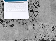 Laptop on concrete floor with various social icons Royalty Free Stock Photos