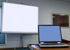 Laptop in conference room. In front of a blank projecting screen royalty free stock photo