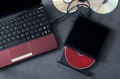 Laptop with connected portable optical drive. Stock Photos