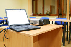 Laptop connected to projector on table Stock Photo