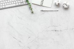 Laptop, cotton branch, notebook on white stone background flat lay copy space. Freelancer, blogger desk workspace. stock images