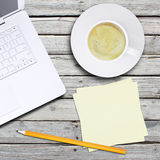 Laptop and a cup of coffee with crema Royalty Free Stock Photos