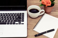 Laptop and cup of coffee with flower on desk Stock Image