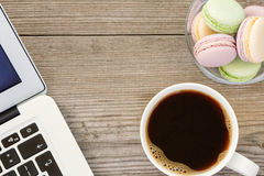Laptop, cup of coffee and french macarons Royalty Free Stock Image