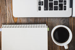 Laptop, a cup of coffee and a notebook lie on a wooden table. Horizontal frame Royalty Free Stock Photos