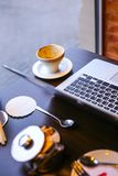 Laptop and cup of coffee on a table. Hipster cafe Royalty Free Stock Images