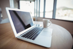 Laptop with cup of coffee on table. In office Royalty Free Stock Photo