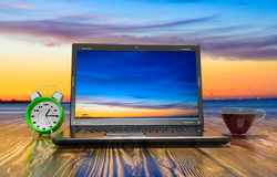 Laptop, cup of hot thea and alarm clock Royalty Free Stock Images