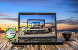 Laptop, cup of hot thea and alarm clock Royalty Free Stock Image