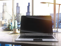 Laptop, cup on table in office through the window glass Royalty Free Stock Image