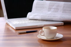 Laptop and a cup of tea. And newspaper on the table royalty free stock photos