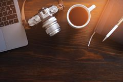 A laptop, a Cup of tea, a camera and a notebook lie on a dark wooden table. The workplace of a photographer or a freelancer. Copy royalty free stock images