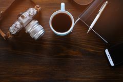 A laptop, a Cup of tea, a camera and a notebook lie on a dark wooden table. The workplace of a photographer or a freelancer. Copy royalty free stock image