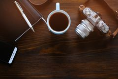 A laptop, a Cup of tea, a camera and a notebook lie on a dark wooden table. The workplace of a photographer or a freelancer. Copy royalty free stock photos