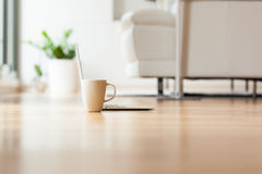 A laptop and cup of tea on the floor in the living room Stock Photo
