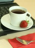 Laptop, cup of tea and strawberry Royalty Free Stock Images
