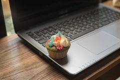 Laptop and cupcakes. On wood table Stock Photography