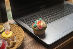 Laptop and cupcakes. On wood table Royalty Free Stock Image