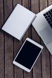 Laptop, cyfrowa pastylka i dzienniczek na drewnianym stole, Obrazy Royalty Free