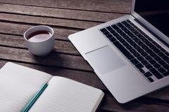 Laptop, czarna kawa i dzienniczek na drewnianym stole, Obraz Stock