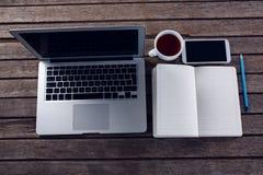 Laptop, czarna kawa, telefon komórkowy i dzienniczek na drewnianym stole, Obrazy Stock