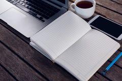 Laptop, czarna kawa, telefon komórkowy i dzienniczek na drewnianym stole, Obrazy Royalty Free