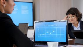 Laptop with data analysis in front of business woman. In the conference room. She looks at the display while talking with her colleagues. Dolly slider 4K stock video footage