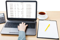 Laptop with data on screen on office table Stock Photography