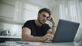 Laptop de datilografia do homem novo em casa Homem de negócios pensativo que usa o computador video estoque