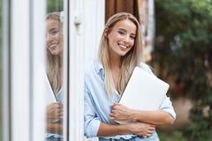 Laptop de sorriso bonito da terra arrendada da menina fotografia de stock