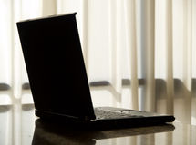 Laptop on a desk. A black laptop on a desk with curtains in the background and smooth light Stock Photo