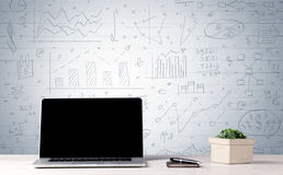 Laptop on desk with business charts on wall Royalty Free Stock Photo