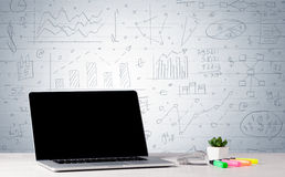 Laptop on desk with business charts on wall Stock Images
