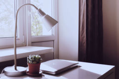 Laptop on desk. Closed laptop and lamp on desk by window with cactus Stock Images
