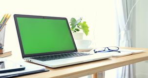 Laptop on desk with green screen. stock video footage