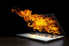 Laptop device damage. Mixed media. Laptop in fire flames on dark background. Mixed media Stock Photography