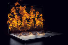Laptop device damage. Mixed media. Laptop in fire flames on dark background. Mixed media Royalty Free Stock Images