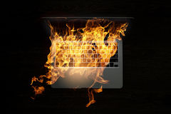 Laptop device damage. Mixed media. Laptop in fire flames on dark background. Mixed media Royalty Free Stock Photography