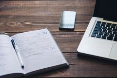 Laptop and diary on the desk Stock Photography