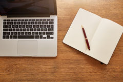 Laptop with diary and pen on work desk Stock Image