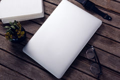 Laptop, diary, pot plant, spectacles and smart watch on wooden table. Overhead of laptop, diary, pot plant, spectacles and smart watch on wooden table Stock Images