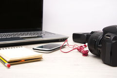 Laptop, digital camera, mobile phone, notebook and earphones on wood table Stock Photography