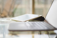 Laptop and digital tablet on a glass table, shallow depth of fie Royalty Free Stock Image