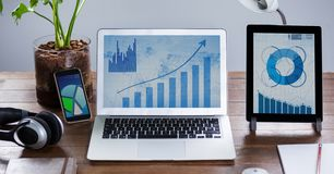 Laptop and digital tablet with graph charts on wooden table. Laptop,digital tablet and mobile phone with graph charts oo wooden table Royalty Free Stock Photography